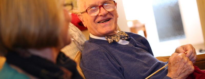 An older man in a bow tie laughs with a friend