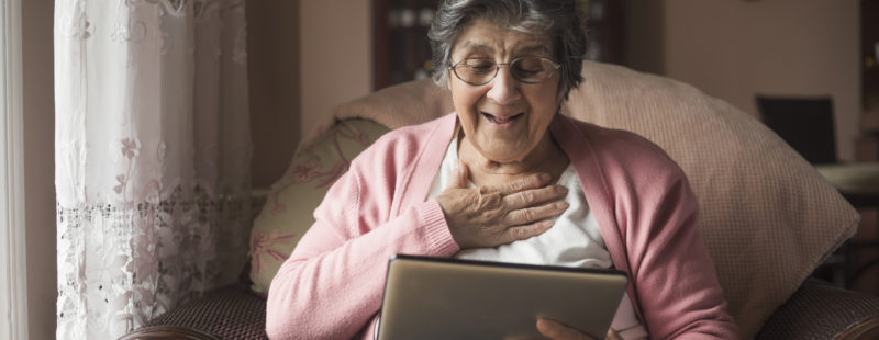 An older woman laughing as she uses a tablet