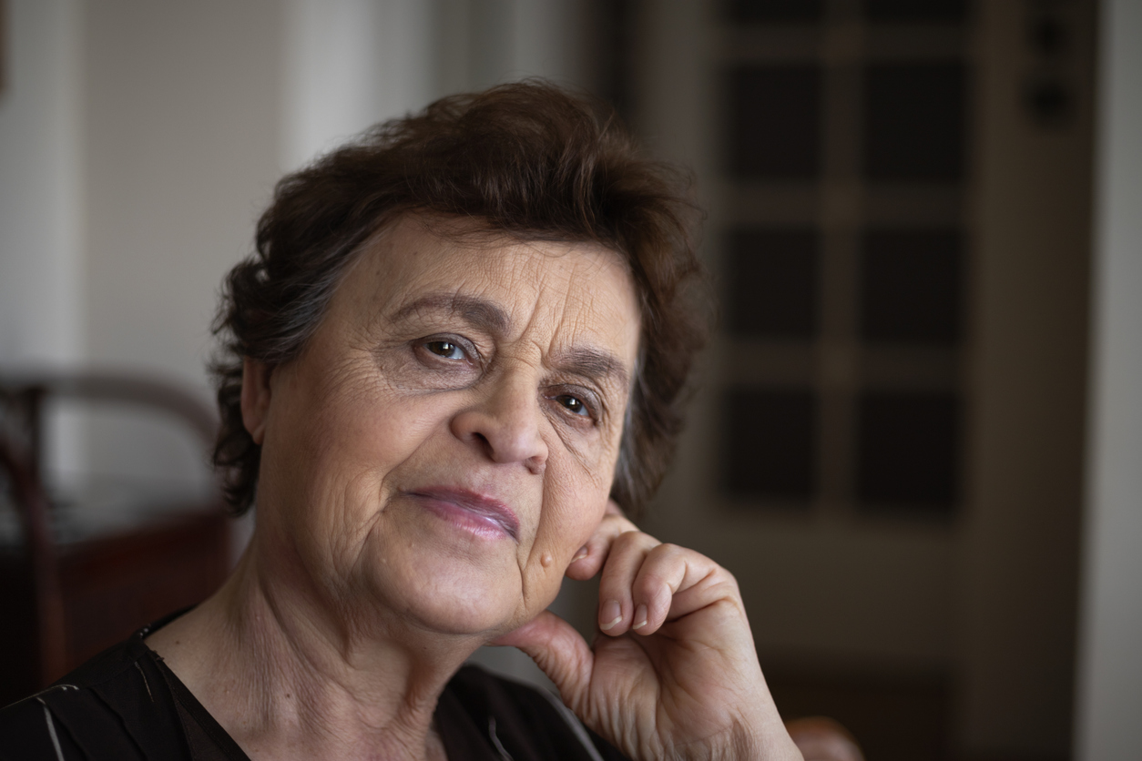 An older women looks pensively at the camera